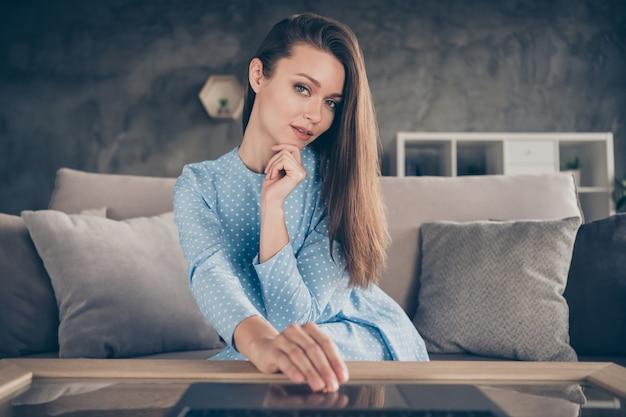 Foto van aantrekkelijke dame pratende laptopcomputer luister vriendje op afstand online videogesprek internetvergadering quarantaine thuis blijven zitten bank dragen blauwe jurk woonkamer binnenshuis