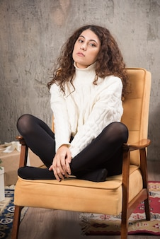 Foto van aantrekkelijke dame zittend in een comfortabele stoel en poseren