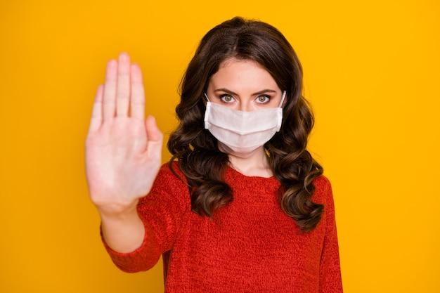 Foto van aantrekkelijke doktersdame hef arm op naar camera express negatieve houding sociaal contact dragen casual outfit beschermend viraal masker geïsoleerd felgele kleur achtergrond