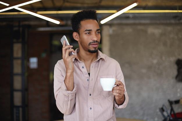 Foto van aantrekkelijke donkere bebaarde, bebaarde man met kort kapsel kopje koffie in opgeheven hand houden, bedachtzaam vooruit kijken en gaan bellen met zijn smartphone