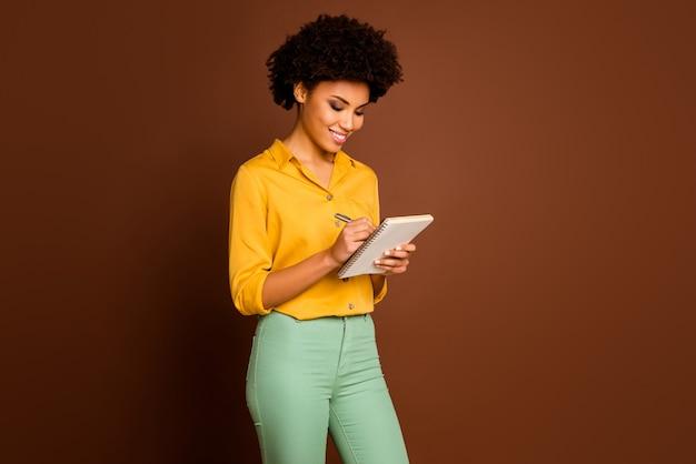 Foto van aantrekkelijke donkere huid krullende dame auteur kijken dagboek creatieve gedachten schrijven commentaar geïnspireerd dragen geel shirt groene broek geïsoleerde bruine kleur