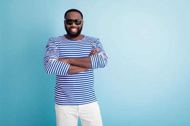 Foto van aantrekkelijke donkere huid man armen gekruist kust strand controle werknemer toothy stralend glimlachen dragen zonnebril gestreepte matroos shirt korte broek geïsoleerde blauwe kleur muur