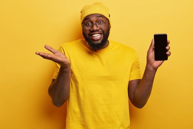 Foto van aantrekkelijke donkere man met brede glimlach, witte tanden, houdt slimme telefoon met leeg scherm voor uw informatie, draagt een ronde bril, werpt handpalm met onzekerheid, neemt een beslissing