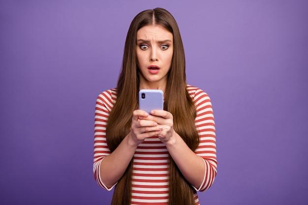 Foto van aantrekkelijke doodsbange dame kijk open mond telefoonscherm lees negatieve opmerkingen blogpost bang slijtage casual gestreept overhemd geïsoleerde pastel paarse kleur muur