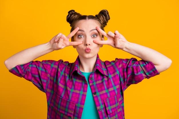 Foto van aantrekkelijke funky tienerdame twee grappige broodjes met v-teken symbolen armen in de buurt van oog verzenden flirterige kokette luchtkussens dragen casual plaid shirt geïsoleerd gele felle kleur achtergrond