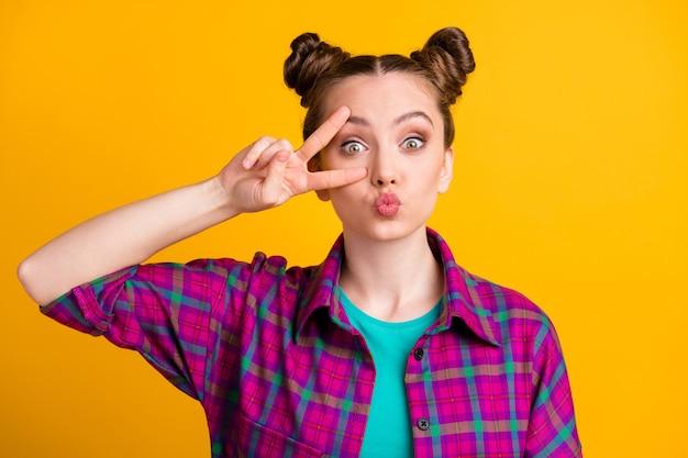 Foto van aantrekkelijke funky tienerdame twee grappige broodjes met v-tekensymbool in de buurt van oog die flirterige kokette luchtkusjes verzendt, draagt een casual geruit hemd geïsoleerd gele felle kleur achtergrond