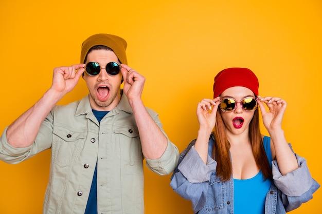Foto van aantrekkelijke gekke dame kerel jonge echtgenoot vrouw samen vakantie doorbrengen opstijgen zonnebril open mond draag casual heldere zomerkleding outfit geïsoleerd felgele kleur achtergrond