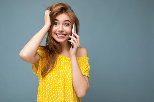 Foto van aantrekkelijke gekke verbaasde verraste jonge vrouw, gekleed in casual stijlvolle kleding staande geïsoleerd over muur met kopie ruimte bedrijf en met behulp van mobiele telefoon.