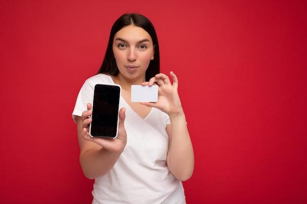 Foto van aantrekkelijke gelukkige jonge brunette vrouw, gekleed in casual wit t-shirt geïsoleerd dan rood