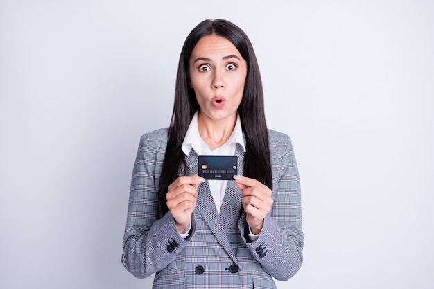 Foto van aantrekkelijke geschokte sprakeloze bankierdame houdt plastic debetcreditcard nieuwe gekke grote commissie banking online overdracht retailservice formalwear geïsoleerde grijze kleur achtergrond