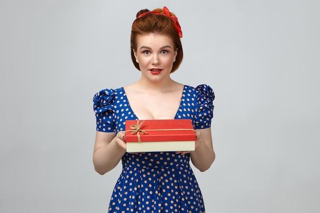 Foto van aantrekkelijke glamoureuze jonge blanke vrouw, gekleed in lichte make-up en elegante blauwe gestippelde jurk, houdt een mooie rode doos vast, kijkt naar de camera en geeft het aan jou als verjaardagscadeau