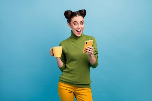 Foto van aantrekkelijke grappige dame houden drank mok ochtend freelance werk browsen telefoon open mond dragen groene coltrui gele broek geïsoleerde blauwe kleur muur