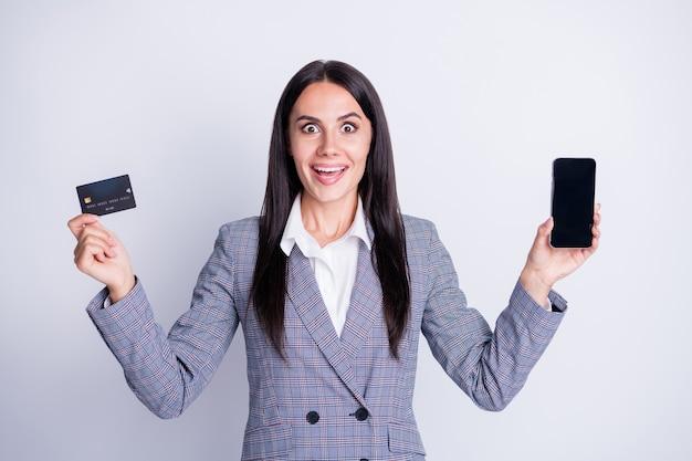 Foto van aantrekkelijke grappige zakelijke dame bezit creditcard debetkaart draadloze betaling retail service geen contact telefoon gadget apparaat app formalwear geruite pak geïsoleerde grijze kleur achtergrond