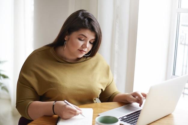 Foto van aantrekkelijke jonge europese vrouwelijke journalist met stijlvolle oorbellen en gebreide trui die aantekeningen maakt in dagboek terwijl ze werkt aan onderzoek voor haar nieuwe artikel, online informatie zoekt