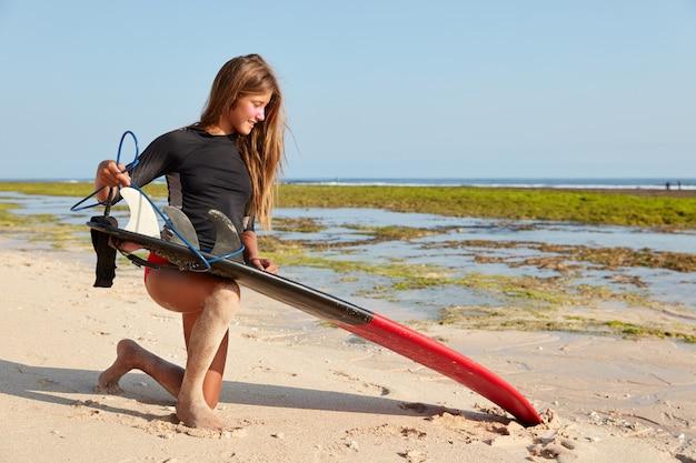Foto van aantrekkelijke jonge vrouwelijke surfer in zwart pak, staat op zand, draagt surfplank, staat in de buurt van de kust, vormt over hemel