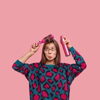 Foto van aantrekkelijke kapper repareert haar, kamt koelkast, gebruikt borstel, bezoekt kapsalon, gekleed in casual outfit