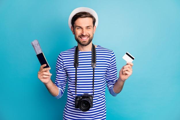 Foto van aantrekkelijke kerel fotograaf houden professionele digitale camera reiziger kaartjes kopen met behulp van creditcard dragen gestreepte matroos hemd vest cap geïsoleerde blauwe kleur
