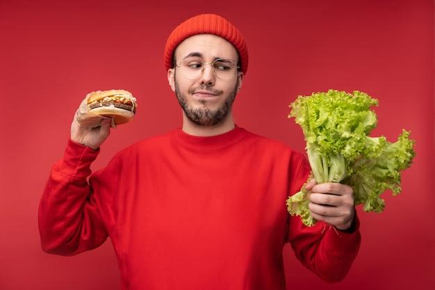 Foto van aantrekkelijke man met baard in glazen en rode kleding. mannetje houdt salade en hamburger, neemt een beslissing tussen gezond en junkfood, geïsoleerd op rode achtergrond.