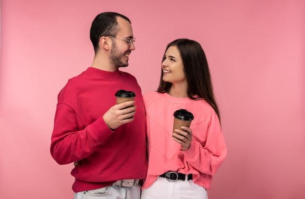 Foto van aantrekkelijke man met baard in rode kleding en vrouw in roze houdt koffie en gawp op elkaar. het paar ziet er gelukkig uit, geïsoleerd over roze achtergrond.