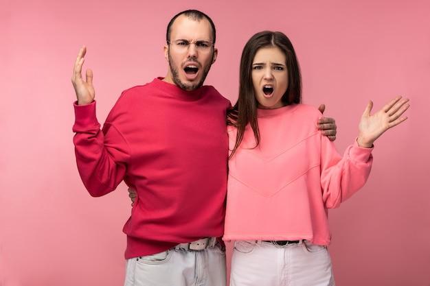 Foto van aantrekkelijke man met baard in rode kleding en vrouw in roze zijn vreselijk zereind, geïsoleerd op roze achtergrond.