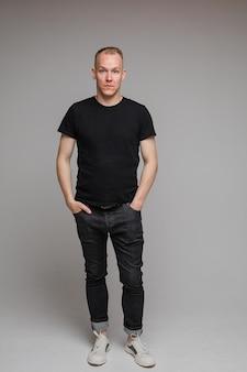 Foto van aantrekkelijke man met een zwart t-shirt en spijkerbroek staat met de handen in de zakken geïsoleerd op een grijze muur