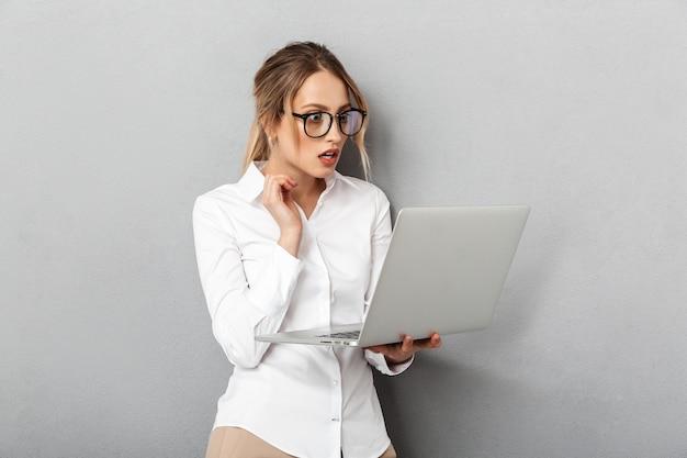 Foto van aantrekkelijke onderneemster die een bril draagt die en laptop in het bureau houdt, geïsoleerd