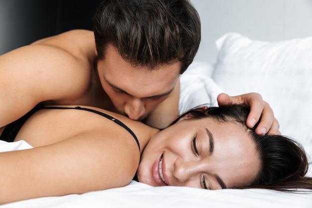 Foto van aantrekkelijke paar man en vrouw samen kussen, liggend in bed thuis of hotel appartement