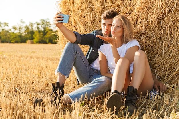 Foto van aantrekkelijke paar man en vrouw selfie te nemen zittend onder grote hooiberg in gouden veld, tijdens zonnige dag