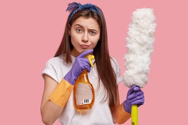Foto van aantrekkelijke roomservice huishoudster houdt reinigingsapparatuur vast, kijkt direct met gefrustreerde uitdrukking