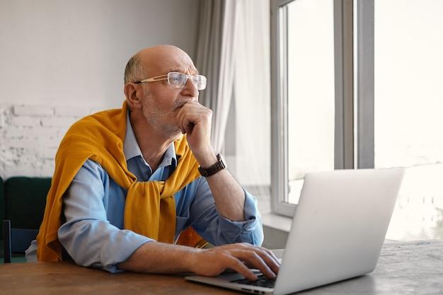 Foto van aantrekkelijke stijlvolle zeventig-jarige senior zakenman dragen bril en formele kleding met doordachte peinzende blik tijdens het werken op laptop pc, zittend aan een bureau bij raam