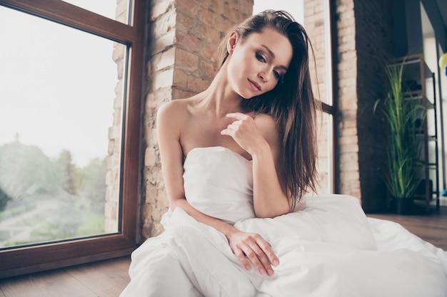 Foto van aantrekkelijke tedere dame thuis blijven bedekt witte deken naakte schouders sensueel uitkleden vriendje videogesprek plagen juffrouw man zit vloer bij raam breng quarantaine binnenshuis door