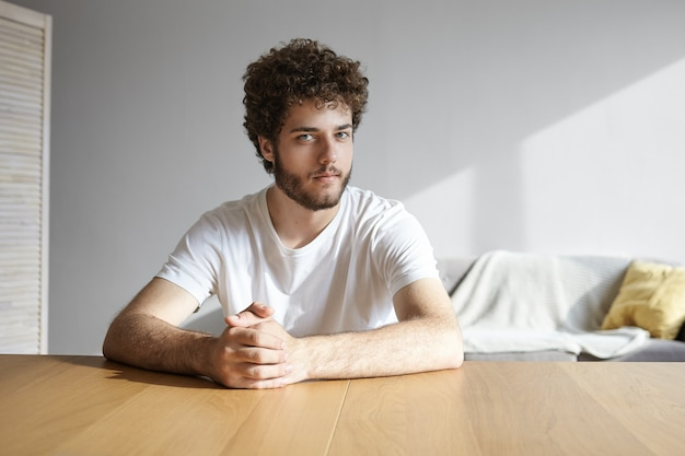 Foto van aantrekkelijke terloops geklede jonge europese bebaarde man gekleed in een wit t-shirt handen gevouwen zittend aan een leeg bureau binnenshuis, met mysterieuze speelse glimlach