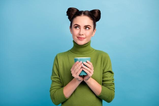Foto van aantrekkelijke tiener dame houden warme drank kopje thee genieten weekend ochtend kijken lege ruimte dromer dragen warme groene coltrui geïsoleerde blauwe kleur muur