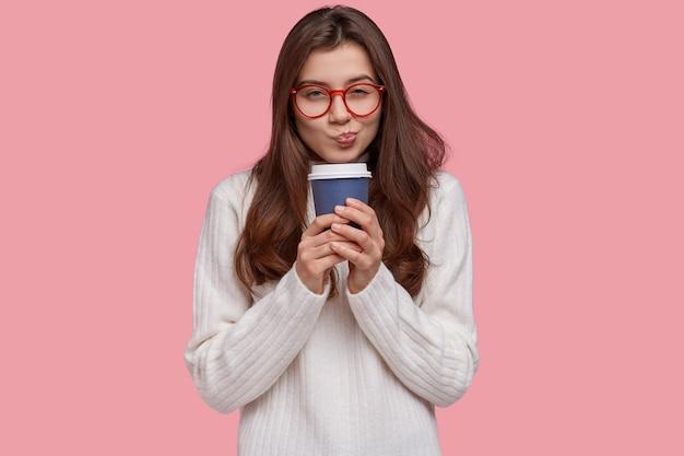 Foto van aantrekkelijke vriendin heeft de intentie om iets te doen, ziet er nauwgezet uit, draagt een bril voor goed zicht, drinkt koffie uit papieren beker
