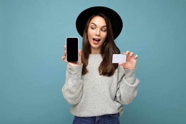 Foto van aantrekkelijke vrolijke jonge brunette vrouw met zwarte hoed en grijze trui geïsoleerd op blauwe achtergrond met creditcard en mobiele telefoon met lege display voor mockup naar de zijkant kijkend.