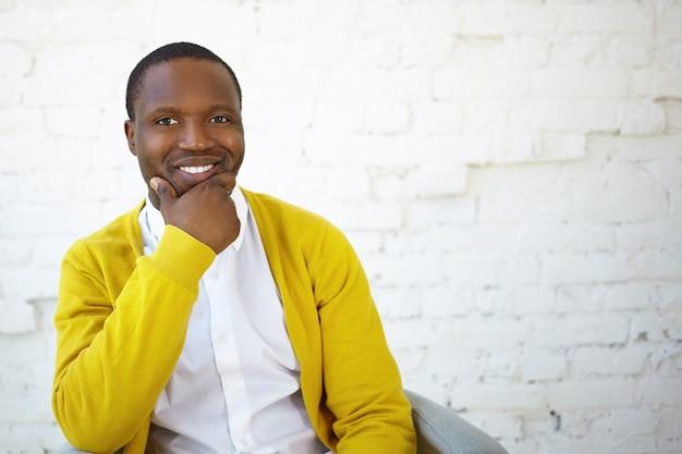 Foto van aantrekkelijke vrolijke zwarte man in geel vest die de hand op zijn kin houdt en breed lacht naar de camera, zich gelukkig of geïnspireerd voelt, zich verheugt op goed positief nieuws, poseren in de studio