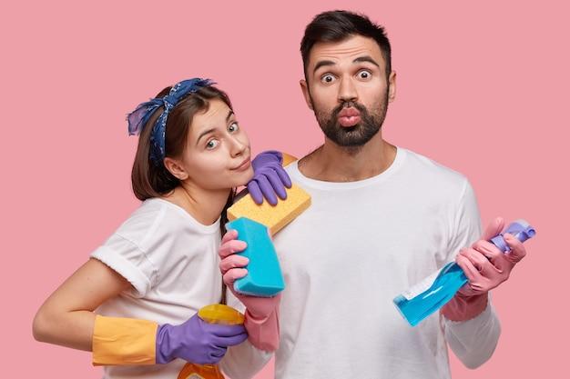Foto van aantrekkelijke vrouw draagt hoofdband, beschermende handschoenen, staat dicht bij echtgenoot die lippen vouwt, sponzen en wasmiddel draagt, huis samen op bestelling brengt