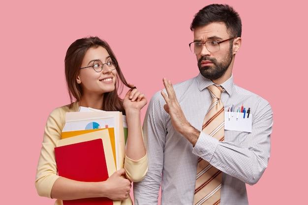 Foto van aantrekkelijke vrouw flirt met haar jonge leraar, draagt papieren en blocnote