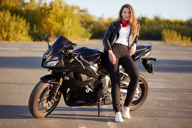 Foto van aantrekkelijke vrouw heeft echt avontuur buiten, staat in de buurt van motor, gekleed in bikers outfit, geniet van zonnige dag