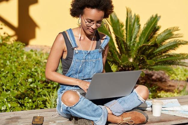 Foto van aantrekkelijke vrouw met afro kapsel, zit gekruiste benen met draagbare laptopcomputer, toetsenborden nieuwe publicatie voor haar blog, luistert naar muziek, maakt gebruik van mobiele telefoon, oortelefoons, draagt stijlvolle kleding
