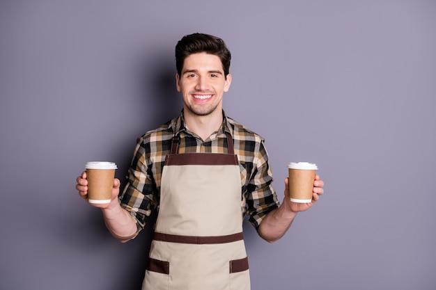 Foto van aantrekkelijke werknemer man hand in hand twee papieren koffiekopjes uitnodigende bezoekers probeer aroma koffie professionele barista slijtage schort geruite overhemd geïsoleerde grijze kleur muur