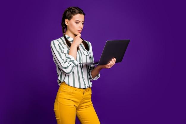 Foto van aantrekkelijke zakelijke dame freelancer bedrijf notebook handen diep nadenken thuistaak uitleg dragen gestreepte shirt gele broek geïsoleerde paarse kleur achtergrond