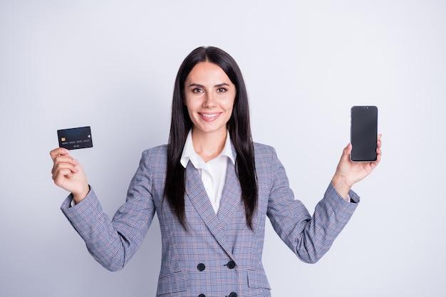 Foto van aantrekkelijke zakelijke dame houdt plastic creditcard retail draadloze betaling geen contact nieuw telefoonmodel gadget apparaat formalwear plaid pak geïsoleerde grijze kleur achtergrond