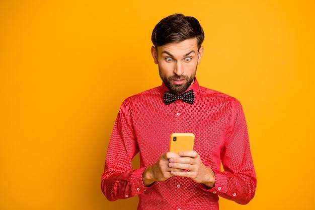 Foto van aantrekkelijke zakelijke kerel telefoon sociaal netwerk werknemer lezing goed nieuws groei blog populariteit draag trendy rood overhemd vlinderdas