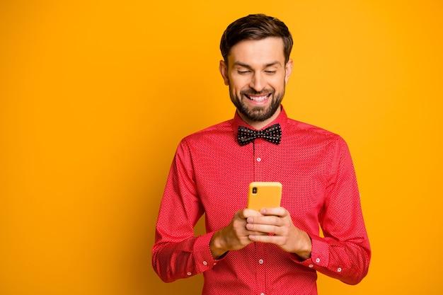 Foto van aantrekkelijke zakelijke man houdt telefoon sociaal netwerk werknemer schrijven advertentie creatieve ontwerper slijtage trendy rood overhemd vlinderdas