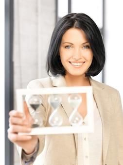 Foto van aantrekkelijke zakenvrouw met zandloper.