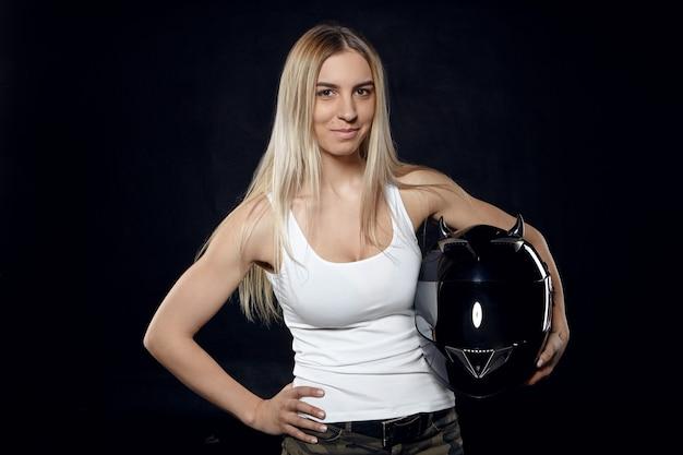 Foto van aantrekkelijke zelfverzekerde jonge vrouw met blond haar en gespierde armen poseren