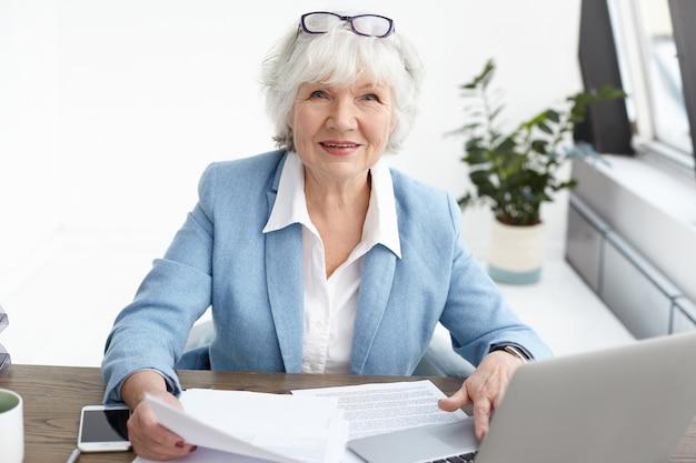 Foto van aantrekkelijke zelfverzekerde oudere volwassen vrouwelijke financieel adviseur met kort grijs haar kijken met glimlach, papier in haar handen studeren terwijl ze aan haar bureau werkt