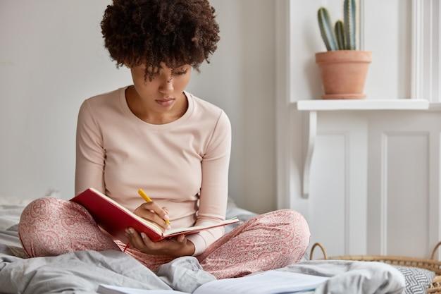 Foto van aantrekkelijke zwarte dame in vrijetijdskleding schrijft verhaal in notitieboekje met pen, houdt benen gekruist, vormt op bed, maakt planning voor volgende week, modellen in slaapkamer. zacht imago. levensstijl
