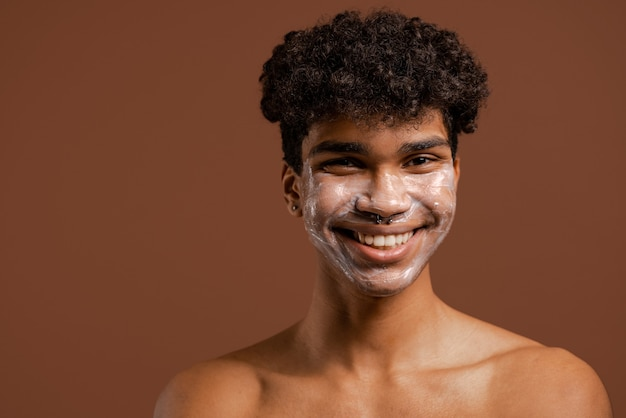 Foto van aantrekkelijke zwarte man met crème of voedingsmasker op gezicht, glimlacht keurig. naakte torso, geïsoleerde bruine kleurenachtergrond.